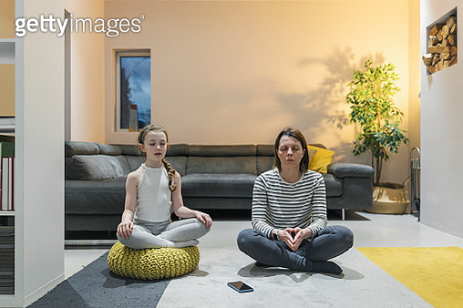 Mother and child practising meditation in living room - gettyimageskorea