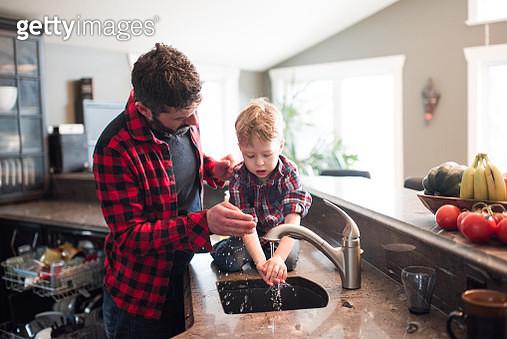 Father watching son wash hands in kitchen sink - gettyimageskorea