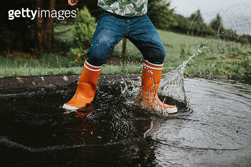 Child wearing orange wellies jumping in a Deep Puddle - gettyimageskorea