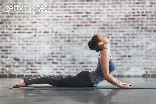Young Woman Doing Yoga Meditation and Stretching Exercises - gettyimageskorea