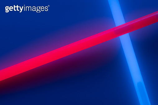 Colorful Glowing Glow Sticks Crossing Pattern on Dark Blue Background. - gettyimageskorea