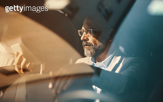 Closeup of late 40's handsome executive man driving in the back seat of a luxury limousine and using a smart phone.  Orange toned image. - gettyimageskorea