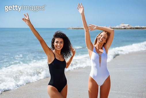 Portrait Of Happy Friends With Arms Raised Standing At Beach During Sunny Day - gettyimageskorea