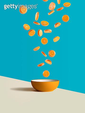 Fresh sliced oranges dropping into orange bowl - gettyimageskorea