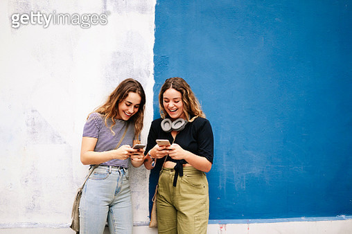 Women with headphones browsing smartphone nearby colorful wall - gettyimageskorea
