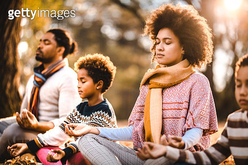 African American family doing Yoga relaxation exercises in autumn day. - gettyimageskorea