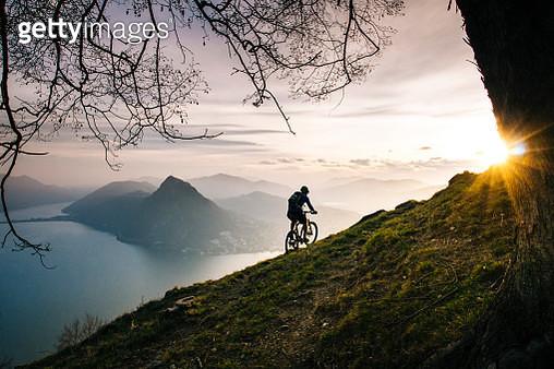 Mountain biker traverses steep mountain slope above lake - gettyimageskorea