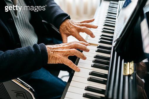 Crop view of senior man playing piano - gettyimageskorea