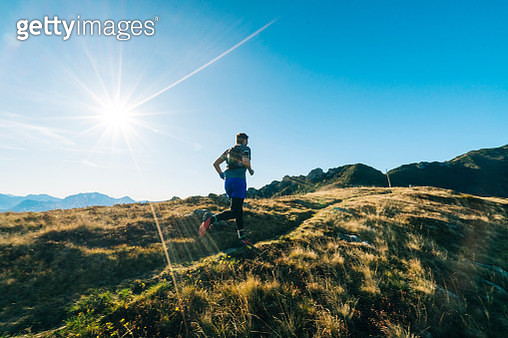 Male trail runner follows path along ridge above valley - gettyimageskorea