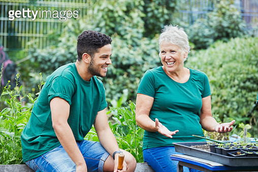 Woman and man laughing in community garden - gettyimageskorea