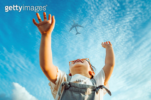 Happy little Asian girl with flower-shaped sunglasses smiling joyfully and raised her hands waving to the aeroplane in the clear blue sky - gettyimageskorea