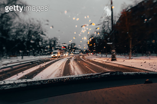 Traffic stands still, on a cold, wet day, shot through a windscreen, focusing on the rain droplets, tailights out of focus - gettyimageskorea