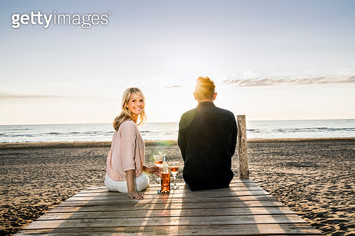Couple with wine glasses sitting on boardwalk on the beach at sunset - gettyimageskorea