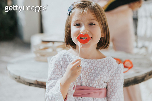 Little girl in white dress playing with photo call card lips at a wedding - gettyimageskorea