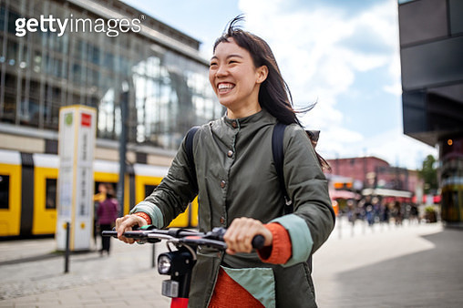 Cheerful woman riding push scooter in city - gettyimageskorea
