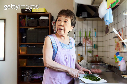 Asian senior woman cutting vegetables with a knife in the kitchen - gettyimageskorea