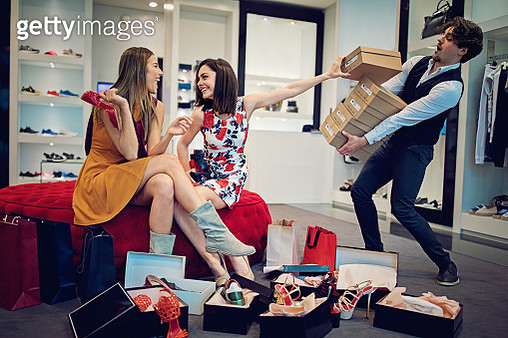 Shopping girls are choosing shoes and asking from salesman for more - gettyimageskorea
