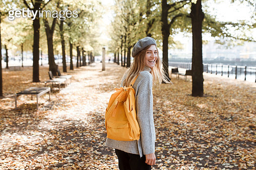 Young woman with yellow backpack in park in Berlin, Germany - gettyimageskorea