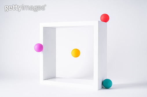 Four Colored Spheres Orbiting Square Frame on White Background. - gettyimageskorea