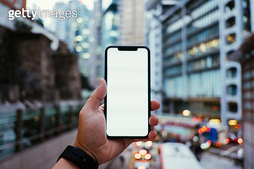 Cropped hand of man holding mobile phone in front of urban skyscrapers in downtown financial district with busy city traffic - gettyimageskorea