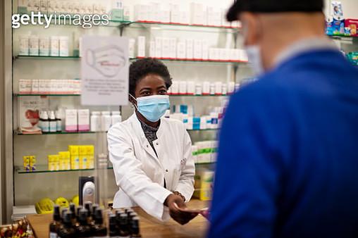 Pharmacist selling medicine to senior man - gettyimageskorea