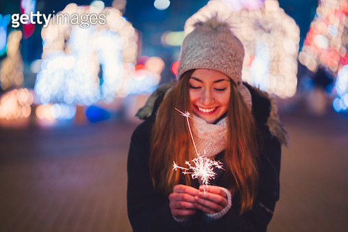 Happy woman at New Year's eve holding burning sparkler - gettyimageskorea