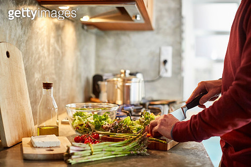 Midsection of man cutting vegetables. Cropped image of male is preparing food. He is working in kitchen. - gettyimageskorea
