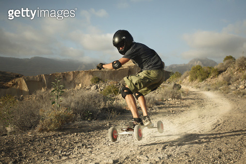 Man landboarding on rocky road - gettyimageskorea