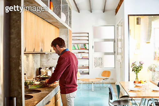 Mid adult man preparing food in kitchen. He is wearing casuals. He is working at home. - gettyimageskorea
