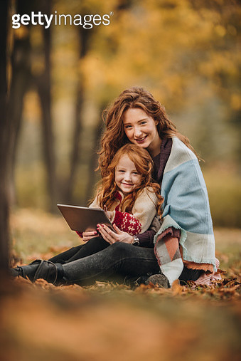 Happy mother and daughter using touchpad in autumn day at the park. - gettyimageskorea