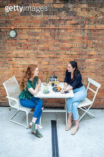 Two women talking in a cafe - gettyimageskorea