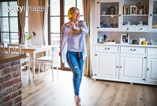 Senior woman with yellow headphones listening to music and dancing at home. - gettyimageskorea