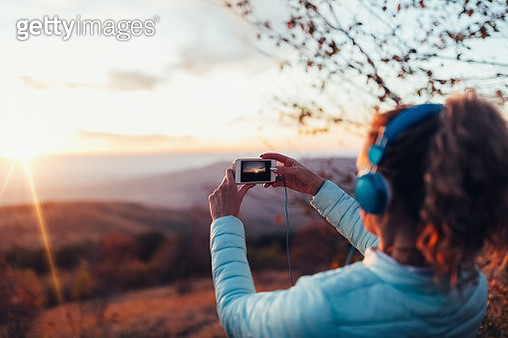 Woman taking photo of the sunset - gettyimageskorea