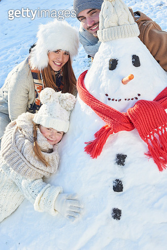 Portrait Of Parents With Daughter Embracing Snowman - gettyimageskorea