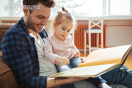 Father reading to his daughter - gettyimageskorea