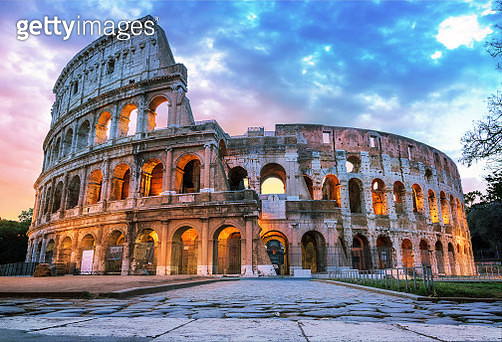 Digital blended image of the ancient roman amphitheatre Colosseum at sunrise, still illuminated by artificial lights, under a cloudy sky, Rome, Italy - gettyimageskorea