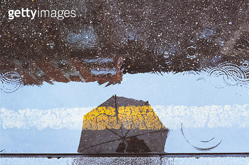 Umbrella reflected in a puddle on a rainy day - gettyimageskorea