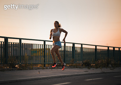 Determined athletic woman jogging on a sidewalk at sunset. - gettyimageskorea