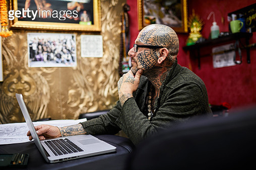 Tattooist with laptop at desk in his studio thinking - gettyimageskorea