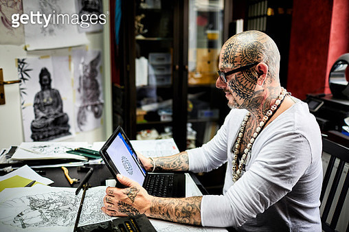 Tattooist using laptop in his studio - gettyimageskorea