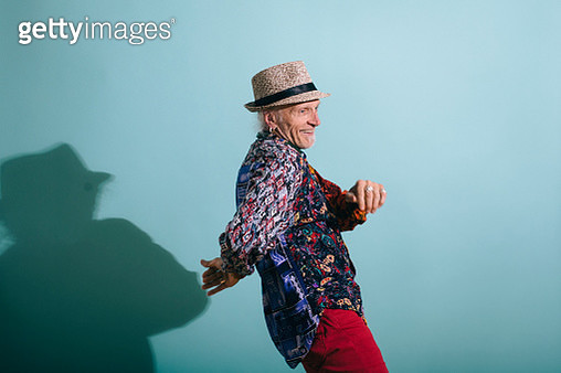 Hip senior gay man in colorful shirt dancing on a Turquoise background laughing and having fun. Part of the LGBTQ Portrait series. - gettyimageskorea