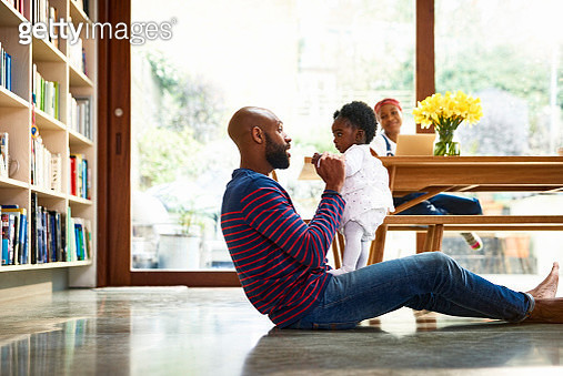 Father playing with baby daughter (6-11 months), woman using laptop at table in background - gettyimageskorea