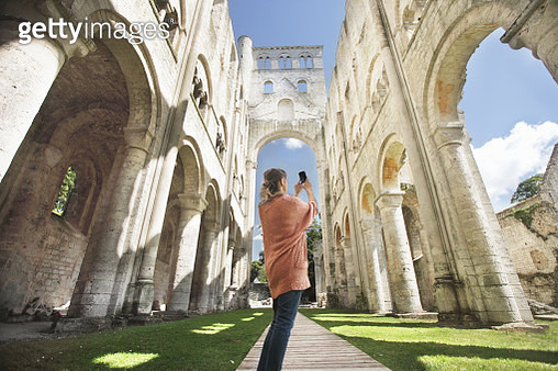 Woman taking picture of cathedral ruins - gettyimageskorea