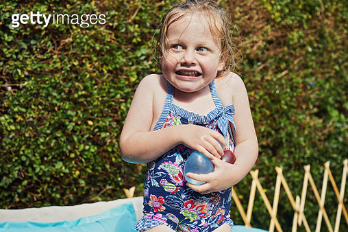Child holding water balloons in a paddling pool - gettyimageskorea