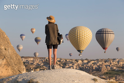 Young woman and hot air ballons, Goreme, Cappadocia, Turkey - gettyimageskorea