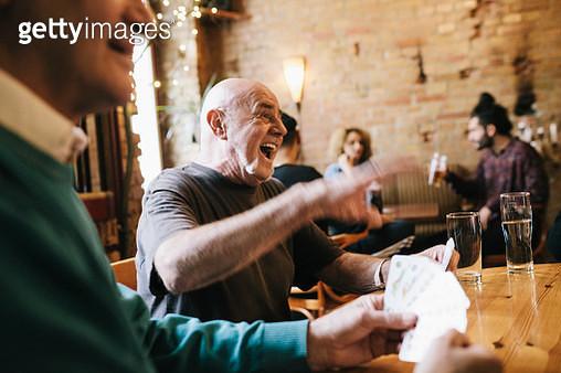 Old Man Laughing During Card Game - gettyimageskorea