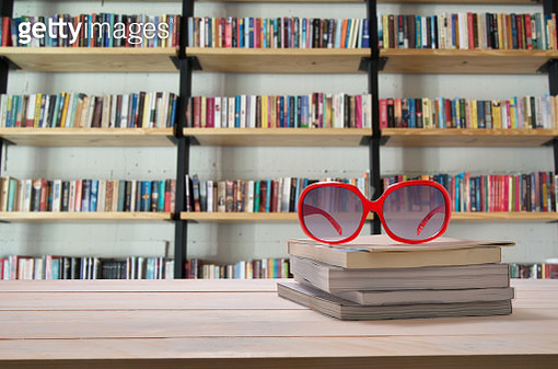 Sunglasses On Stacked Books Over Table In Library - gettyimageskorea