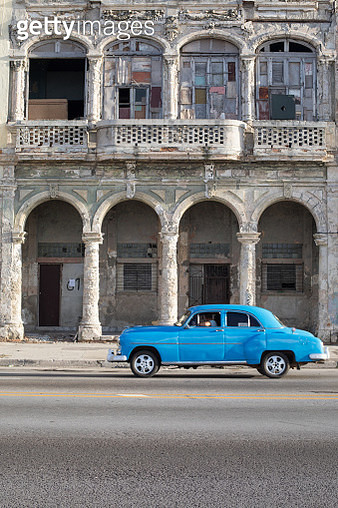 A blue classic car drives past dilapidated buildings on the seafront of Havana, the Capital of Cuba. - gettyimageskorea