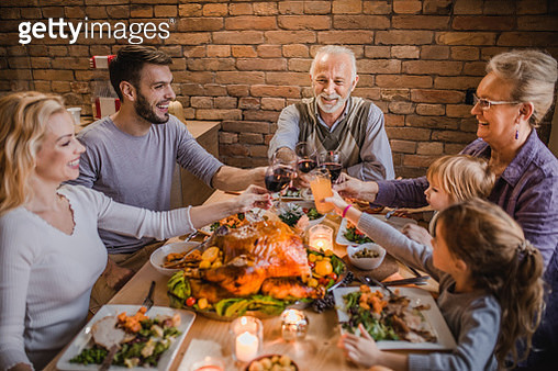 Happy extended family toasting while having a Thanksgiving dinner party in dining room. - gettyimageskorea