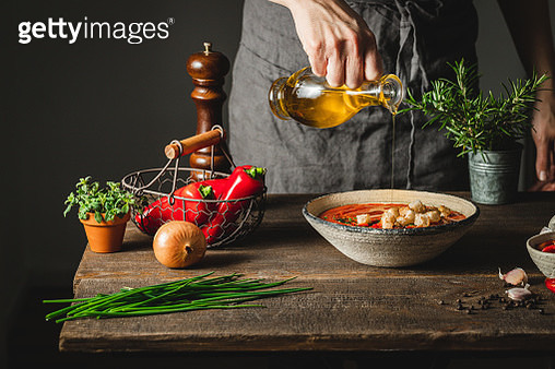 Chef adding olive oil in red pepper soup pot - gettyimageskorea